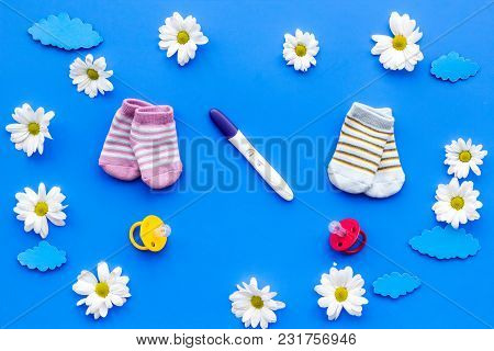 Pregnancy Test, Socks And Flowers On Blue Background Top View