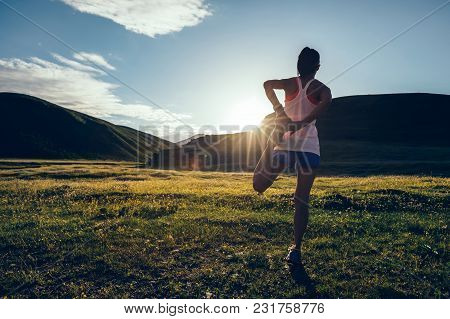 Young Fitness Woman Runner Warming Up On Sunset Grassland Trail