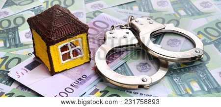 Small Toy House And Handcuffs Is Lies On A Set Of Green Monetary Denominations Of 100 Euros. A Lot O