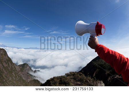 Hand Hold Loudspeaker Over Blue Sky On Mountain Peak