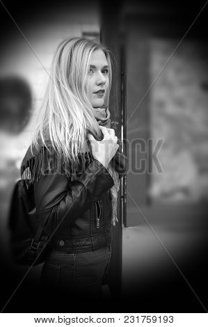 Cold. A Beautiful Blonde Girl Is Standing At A Public Transport Stop. The Girl Is Dressed In A Black