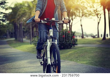 woman cyclist riding bike in tropical park