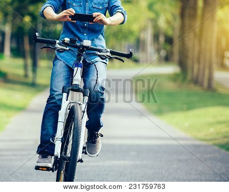 Cyclist Use Cellphone While Riding Bike In Tropical Park