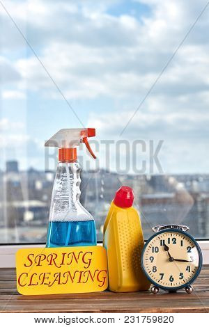 Cleaning Concept With Supplies. Spray For Window Cleaning, Alarm Clock And Message With Text Spring