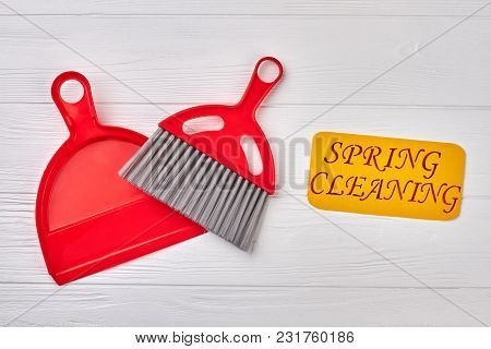 Spring Cleaning Concept With Supplies. Red Plastic Scoop And Brush On White Wooden Background. Clean