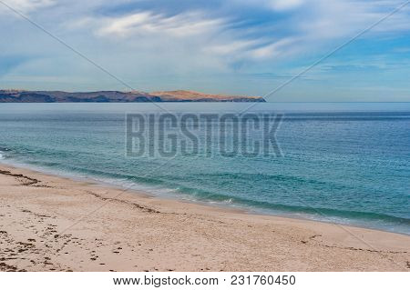 Calm Sea And Sand Beach With Distant Hills And Dolphin Backs In The Water On Clear Day. Picturesque