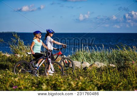 Women riding bicycles at seaside