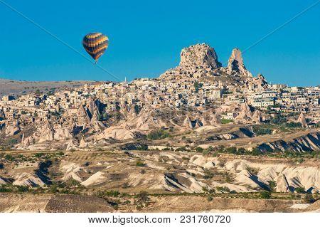 Hot air balloon flying over Cappadocia near Uchisar castle at sunrise, Turkey