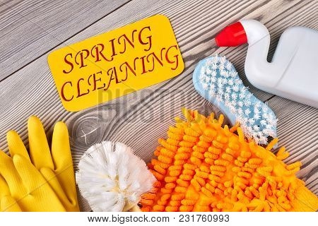 House Cleaning Items On Wooden Background. Set Of Equipment For Spring House Cleaning. Cleaning Serv