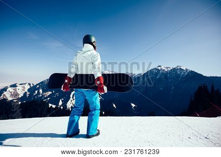 One Snowboarder With Snowboard On Ski Slope Ready For A Descent