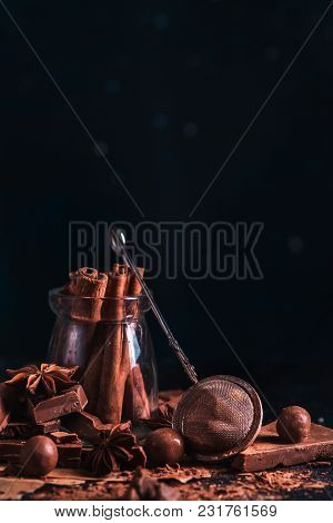 Dessert Ingredients Close-up. Cinnamon In A Glass Jar, Scattered Cocoa Powder And Pieces Of Broken C
