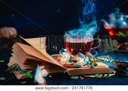 Steaming Cup Of Tea On An Open Book With Magical Burning Flowers. Fantasy Reading Concept. Dark Stil