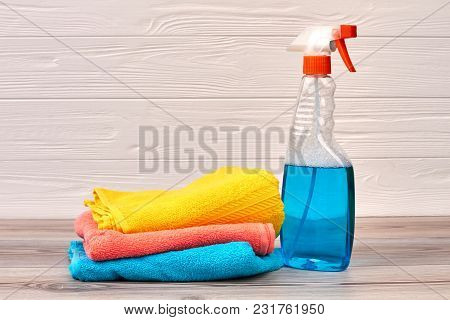 Cleaning Spray Bottle With Plastic Dispenser. Window Cleaner And Colorful Rags O Wooden Background.