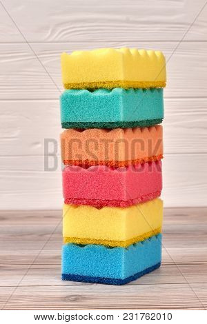 Stack Of Multicolored Kitchen Sponges. Six Stacked Colorful Kitchen Sponges On Light Wooden Backgrou