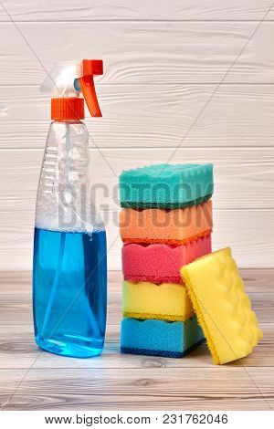 Cleaning Sponges And Plastic Bottle Of Spray. Sponges Near Blue Plastic Spray Detergent Bottle On Wo
