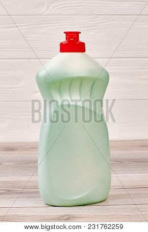 Bottle With Liquid For Dish Washing. Green Plastic Detergent With Red Cap Close Up. Eco-cleaning Con