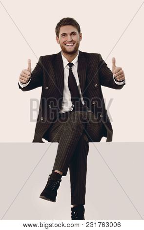 handsome businessman sitting and showing thumbs up.