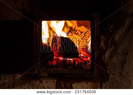 Burning Flame Of A Furnace In A Russian Village. Warmth And Comfort In The House
