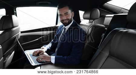 smiling businessman sitting in the back seat of a prestigious car