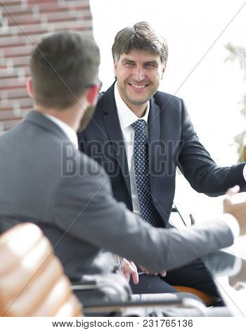Close-up of a senior manager talking to a colleague.
