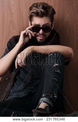 Confident man sitting on the floor on a wooden background