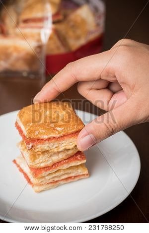 Hand Picking Piece Of Strawberry Puff From Dish For Eating