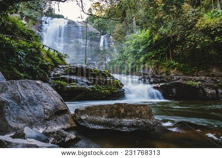 Natural Background Waterfall Flow. Travel Nature. Travel Relax Waterfall. In The Summer.  Thailand