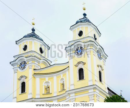 Twin Towers And Clocks At Midday With Statues In Niches  Of Yellow And White Facade  Of St. Michael