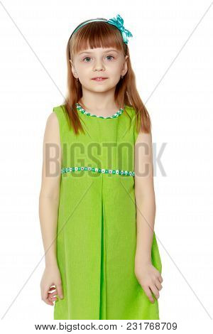 A Little Girl With Long Blond Hair And A Short Bangs, In A Short Summer Dress.the Girl Is Standing I