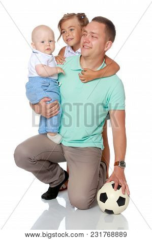 Happy Dad With Young Children. The Concept Of The Upbringing Of Children, A Friendly Family, The Dev