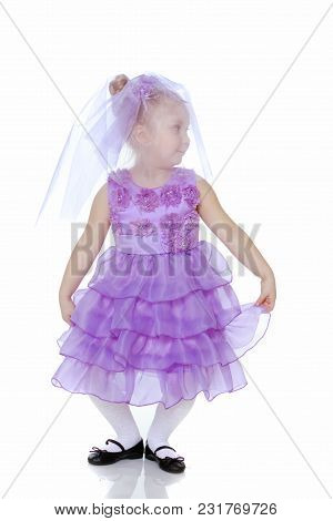 A Sweet Little Round-faced Girl In A Smart Purple Dress. With A Veil Covering His Face.she Makes A C