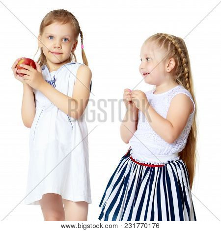 Two Cute Little Girls With Apples, In The Studio On A White Background. Concept Of Happy Childhood,