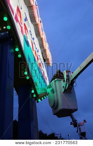 Las Vegas, Nevada / 3-15-2016: Workmen apply green a green sheet of Plexiglas to the world famous Welcome to Las Vegas Sign to celebrate St. Patrick's Day on Saturday March 17, 2018.
