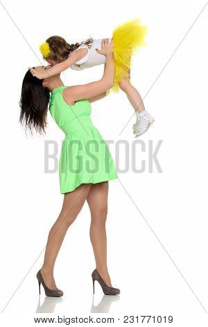 Beautiful Young Mother In A Short Green Dress And Her Little Beloved Daughter In A Yellow Skirt.fun