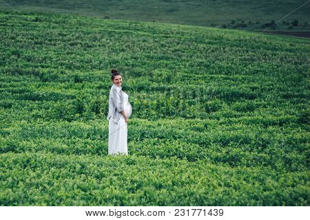 Happy Pregnancy Young Women Standing In Green Field In White Dress