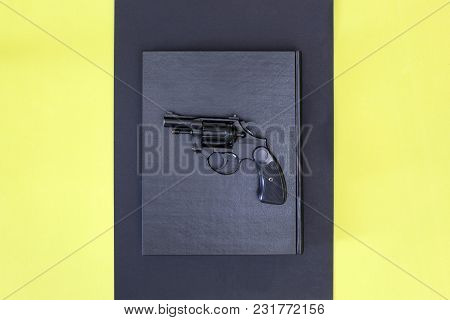 Revolver And Black Book On A Colored Background