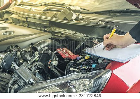 Man Writing Note On Book, Paper Or Notepad With Blurred Engine Background.for Automotive, Transporta
