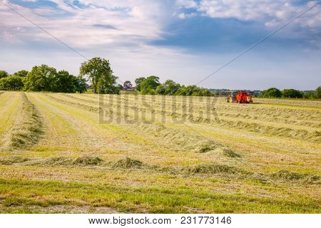 English rural landscape with  tractor collecting cut hay making silage bales Southern England UK