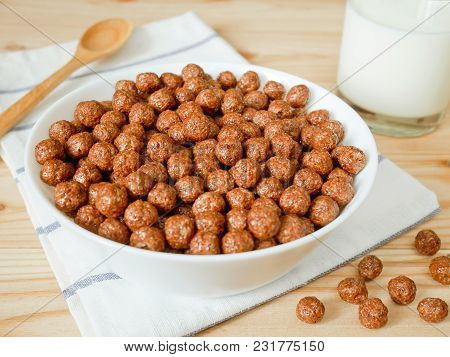 Chocolate Cereal Balls In A Bowl And A Glass Of Milk. Healthy Breakfast Concept.