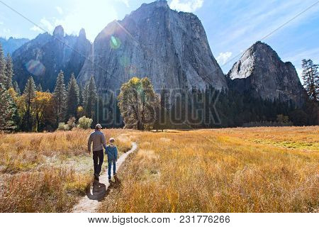 Back View Of Active Family Of Two, Father And Son, Enjoying Valley And Mountain View In Yosemite Nat
