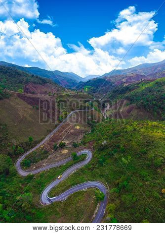 Top View Of Green Field Mountain Forest And Winding Curve Road Transportation For Background, Scenic