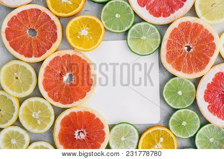 Top View Paper Sheet With Sliced Citrus Fruit On Light Background. Flat Lay. Summer Background