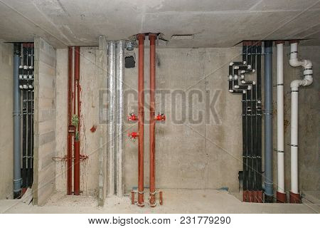 Pipes Of Heating And Water Supply System On The Background Of A Concrete Wall.