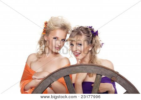 two young blond woman with flowers in hairs smile