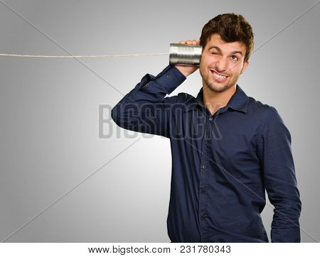 Young Man Listening From Tin Can Phone On Grey Background