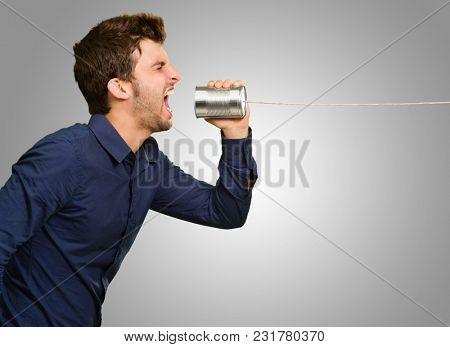 Man Shouting In Tin Can Telephone On Grey Background