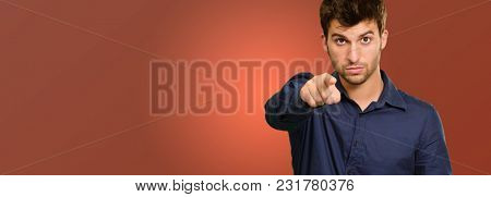 Portrait Of Man Holding Clipboard And Gesturing On Coloured Background