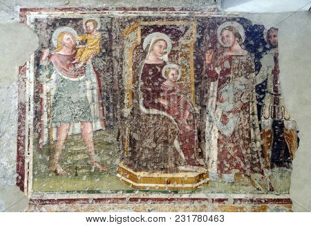 VERONA, ITALY - MAY 27: Enthroned Madonna and Child, Saints Christopher, Catherine, George and a worshipper Knight, fresco in the church of San Pietro Martire in Verona, Italy, on May 27, 2017.