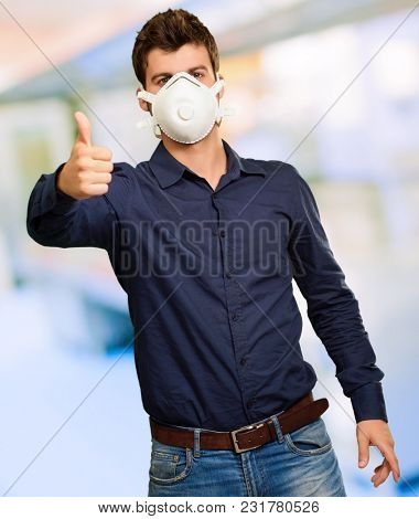 Young Man Gesturing And Wearing Mask, Indoors