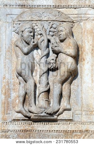 VERONA, ITALY - MAY 27: Adam and Eve eat the fruit of the forbidden tree, medieval relief on the facade of Basilica of San Zeno in Verona, Italy, on May 27, 2017.